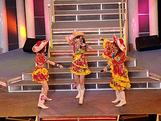 Eri Kamei - Aika Mitsui (left), Sayumi Michishige (center), and Kamei performing at Morning Musume's Platinum 9 Disc concert tour in May 2009
