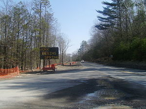 New York State Route 28A - NY 28A at Monument Road before the reconstruction of the highway. A virtual message sign mentions construction beginning in the spring.