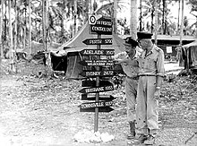 """Two men in light-coloured uniforms with a sign reading """"Perth 5290, Adelaide 3507, Young & Jacksons Pub Melbourne 2990, Sydney 2472, Brisbane 1955, Townsville 1237"""""""