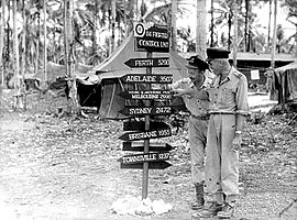 "Two men in light-coloured uniforms with a sign reading ""Perth 5290, Adelaide 3507, Young & Jacksons Pub Melbourne 2990, Sydney 2472, Brisbane 1955, Townsville 1237"""