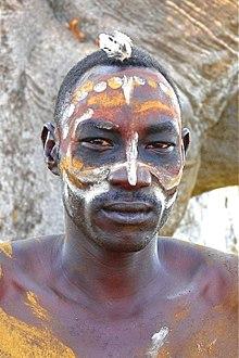 un homme avec le visage paint d'ocres et de blanc