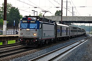 Silver and blue locomotive with passenger cars passing through a station