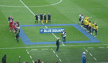 Two football teams line up opposite each other on the halfway line, with the referee, assistants and the fourth official standing to their side