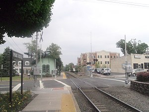 Park Ridge station (NJ Transit) - The Park Ridge station on the Pascack Valley Line facing northbound along the tracks. The former Erie Railroad depot is visible in the distance and the two-side of street platform is noticeable.