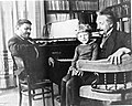 Paul Ehrenfest on the Hupfeld grand piano with Paul junior and Albert Einstein, Leiden, 1920.jpg