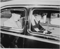 Photograph of General Dwight D. Eisenhower and Mrs. Eisenhower, smiling in the back of a limousine. - NARA - 199122.tif