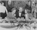 Photograph of movie stars Angela Lansbury, Charles Coburn, and Constance Moore, seated at a table during a Roosevelt... - NARA - 199325.tif