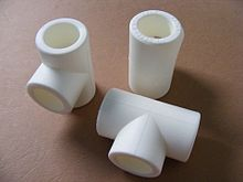 Three white plastic fittings: two tees and a union