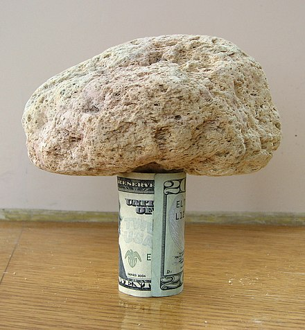 A 15-centimeter (5.9 in) piece of pumice supported by a rolled U.S. $20 bill demonstrates its very low density. Pumice on 20 dollars.jpg