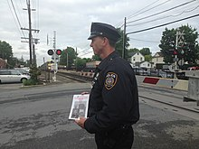 A police officer wearing a dark blue uniform faces left, holding a white pamphlet. Behind him a grade crossing gate is down, red lights are on and a train is approaching