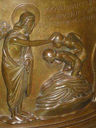 Baptismal font at St Bartholomew's Church, Liège - Detail of John the Baptist baptising the two neophytes.
