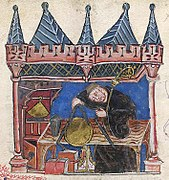 Enluminure d'un homme en habits de moine mesurant un disque doré posé sur une table avec un compas. Des livres et une mitre sont posés sous la table et la pièce se trouve dans ce qui ressemble à un château.