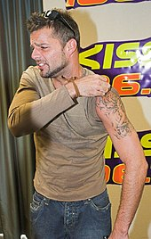 Ricky Martin looking to his right, while pulling up his the left sleeve of his t-shirt to reveal a tattoo.