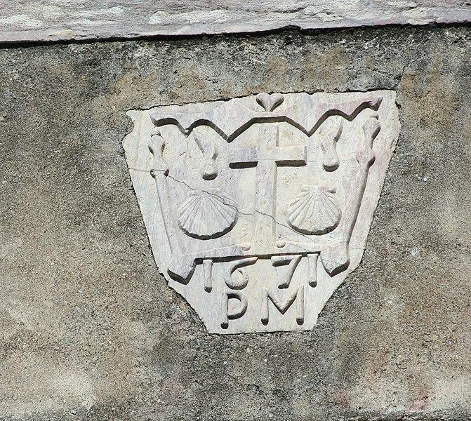 Riols (Hérault) - cartouche en marbre inséré dans une façade et associé au pèlerinage de Saint-Jacques. Sont représentés: deux coquilles St-Jacques, deux bourdons, deux gourdes, un cœur, la date 1671, les initiales PM.