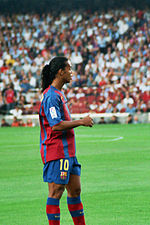 Suntanned man with a long-haired hair, wearing a red and blue football shirt. In the background green grass is rarely visible.
