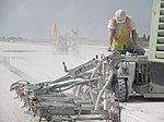 Runway construction worker operating a dowel drilling machine.jpg