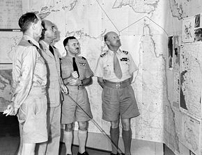 Four men in summer military uniforms in front of a map of northern Australia