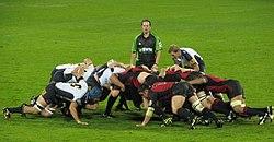 Dwie przeciwstawne formacje ośmiu mężczyzn, w kolorze białym i czarnym w lewo, czerwony i czarny w prawo, przed naciśnięciem siebie w przykucnął pozycji;  za nimi stoi innego zawodnika Arbiter