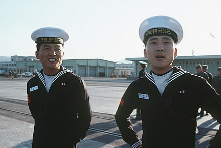 "ROKN seamen in the early 1980s. The lettering on their hats reads ""Republic of Korea Navy"" in Korean. South Korean sailors 1981.jpeg"
