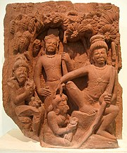 A brown stone sculpture. Rama sits on a stone under a tree (right, largest figure) with a bow in left hand and the other hand on the head of Ahaya(centre bottom), who is seated on the ground with flowers in her hand. Behind her stands Lakshamana. The leftmost figure is of Vishvamitra sitting on a stone.