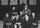 Posed group black-and-white photograph of seven Chinese men, possibly academics, in formal wear: two wear European-style suits, the five others wear Chinese traditional dress; four of the seven sit on the floor in the foreground; another sits on a chair behind them at centre-left; two others stand in the background. They surround an eighth man who is robed, bearded, and sitting in a chair placed at centre-left. Four elegant window are behind them in a line