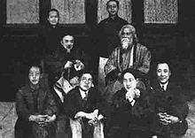 Posed group black-and-white photograph of seven Chinese men, possibly academics, in formal wear: two wear European-style suits, the five others wear Chinese traditional dress; four of the seven sit on the floor in the foreground; another sits on a chair behind them at centre-left; two others stand in the background. They surround an eighth man who is robed, bearded, and sitting in a chair placed at centre-left. Four elegant windows are behind them in a line.