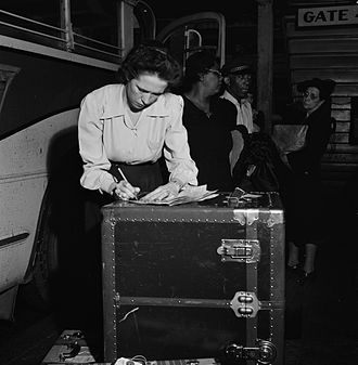 Tennessee Coach Company - A baggage agent checking bags at the Greyhound station in Knoxville, 1943 by Esther Bubley.