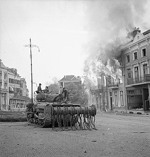 Liberation of Arnhem - A Sherman Crab Flail Tank outside burning buildings in Arnhem, 14 April.