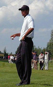 Un joueur de golf, casquette noire sur la tête, tient une balle dans sa main droite.