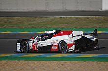 A side view of the Toyota TS050 Hybrid Le Mans Prototype 1 racing car with the number 7 inside a red triangle painted to the right of the front-left wheel