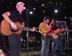 Three man on stage playing three different guitars.