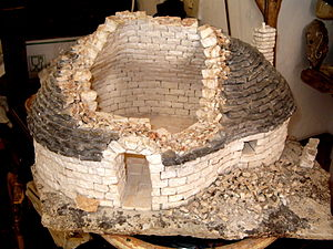 Trullo - Model showing the typical construction technique of a trullo of Alberobello; the cavity between the inside ashlar wall face and the exterior covering of stone tiles or chiancharelle, is filled with stone rubble and the vault is one of stone voussoirs.