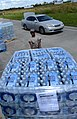 U.S. Air Force Airman 1st Class Johnny L. Carter, with the 159th Medical Group, Louisiana Air National Guard, moves a pallet of bottled water to be distributed to residents Sept 120902-N-CT127-038.jpg