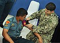 U.S. Navy Hospital Corpsman 2nd Class Arman Hajiomar, right, with Maritime Civil Affairs and Security Training Command, demonstrates how to use a tourniquet during a subject matter expert medical symposium 130522-N-NX489-139.jpg
