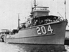 "A black-and-white photograph of the USS Thrush floating near other structures. The boat is facing the camera with its prow facing the right of the photo, displaying ""204"" painted on its starboard hull."