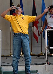 A man in a baseball cap, yellow T-shirt and blue jeans singing into a microphone with his arms spread wide