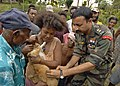 US Navy 070810-N-4954I-120 Lt. Col. Raveesh Chhajed, a veterinarian from the Indian Army, gives a family cat a rabies vaccination while onlookers gather to see the procedure.jpg