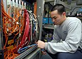 US Navy 080823-N-9079D-042 Information Systems Technician 3rd Class Justin K. Sin, from Honolulu, Hawaii, terminates connectors on a SIPRNET switch in the tactical automated information systems center aboard the aircraft carrie.jpg