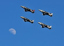 Four jet aircraft formatting in a nose-up attitude with the Moon at the bottom left hand corner.