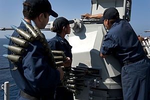 US Navy 111231-N-KS651-228 Sailors load a Mk 38 Mod 2 25mm machine gun system aboard amphibious dock landing ship USS Pearl Harbor (LSD 52).jpg