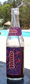 a bottle of Vimto with a straw placed on a table near a swimming pool on a sunny day