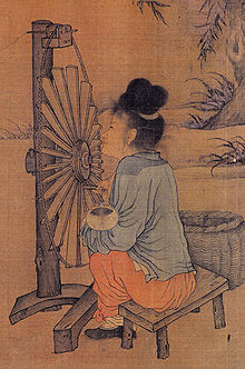 An older woman sits in front of a machine consisting of a vertically aligned wheel composed of about two dozen flat wooden spokes, with a string for an outside rim. The wheel is held up by a simple wooden pole stand.