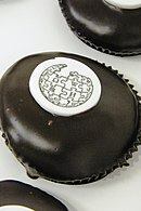 A chocolate covered cupcake topped with the Wikipedia logo stenciled on a white chip