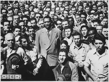 "Robeson leading Moore Shipyard (Oakland, California) workers in singing the ""Star Spangled Banner"", September 1942. Robeson, too, was a shipyard worker in World War I. ""Paul Robeson, world famous Negro baritone, leading Moore Shipyard (Oakland, CA) workers in singing the Star Spangled Ba - NARA - 535874.tif"