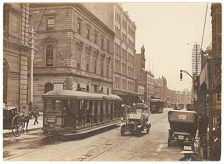 A tram car on George Street in 1920. Sydney once had one of the largest tram networks in the British Empire. (Looking north along George Street (with tram, T-model Ford and hansom cab) from Union Line Building (incorporating the Bjelke-Petersen School of Physical culture), corner Jamieson Street), n.d. by (5955844045).jpg