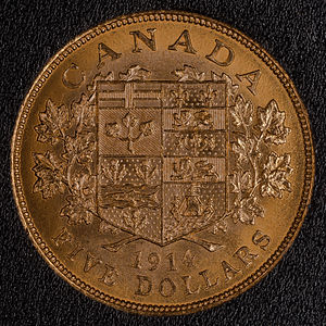 Canadian dollar - $5 gold Canadian coin from 1914. Reverse side shown depicting a shield with the arms of the Dominion of Canada. The coin weighs 8.36 grams and is 90% gold giving it 7.524 grams of gold. It has a diameter of 21.59 mm and a thickness of 1.82 mm at the rim.