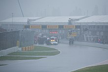 The area is saturated with heavy rain and all cars are stopped behind the safety car.