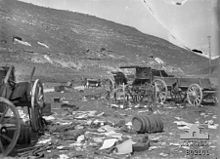 Cart wheels, wagons destroyed barrels and other wreckage in foreground, two soldiers on the road in the middle distance near a staff car