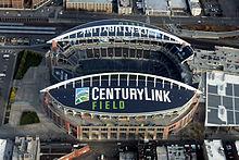 Vedere aeriană a unui stadion gol cu arcuri proeminente.  Zona înconjurătoare are căi ferate, o piață și un garaj.