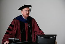Middle-aged, bespectacled man in academic dress making a presentation